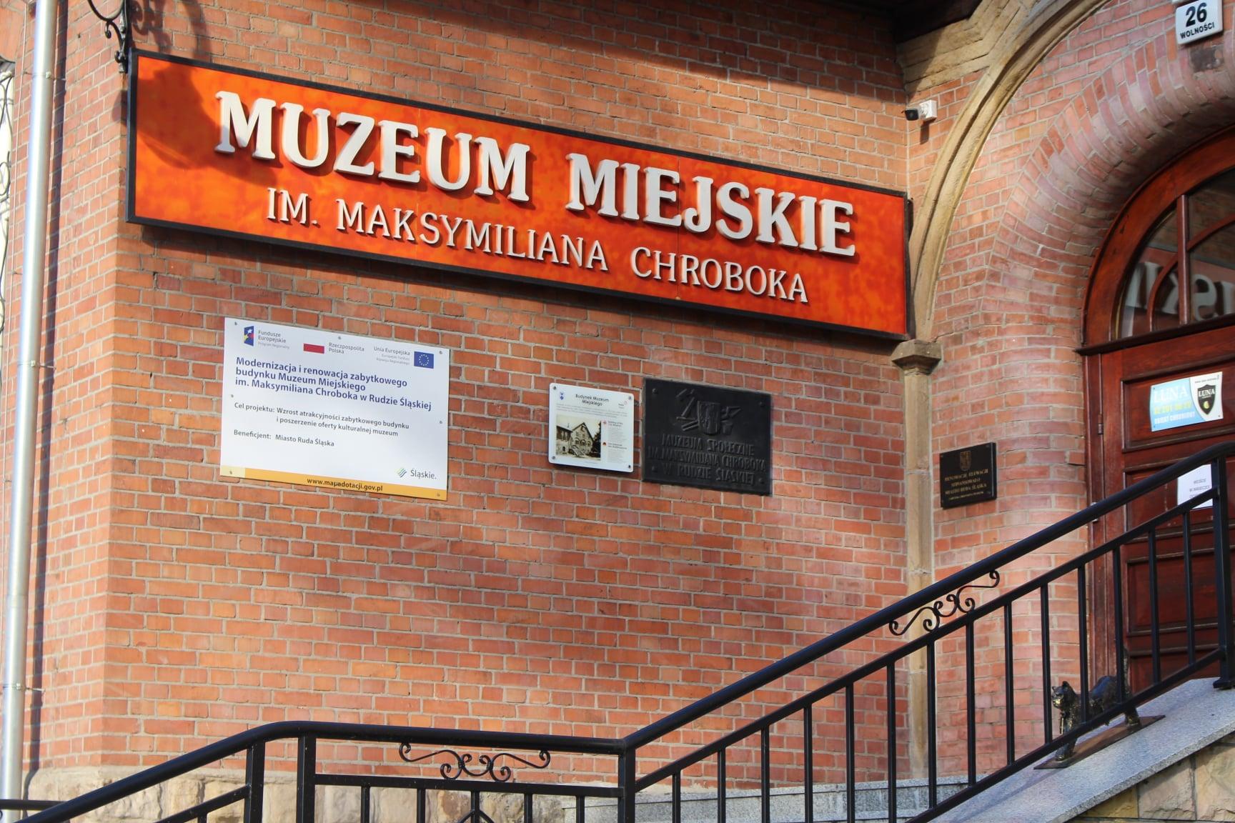 """Fragment budynku z cegły z napisem """"Muzeum Miejskie im. Maksymiliana Chroboka"""" i tablicami informacyjnymi, schody z poręczą prowadzące do brązowych drzwi"""